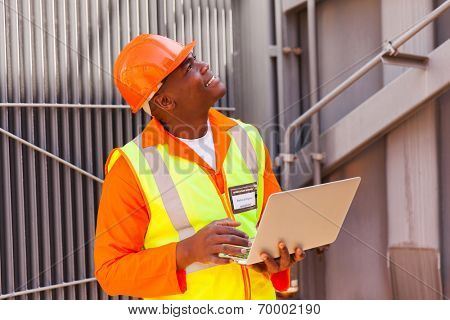 african electrical engineer using laptop in substation