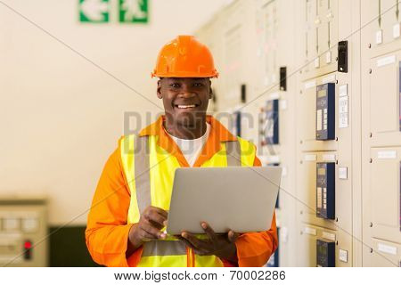 happy african electrical engineer with laptop computer in power plant control room