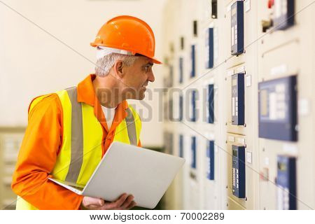 middle aged industrial electrician working in power plant control room