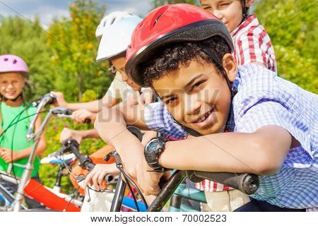 Smiling boy in helmet holds handle-bar of bike