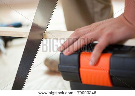Man's Hands Using Handsaw