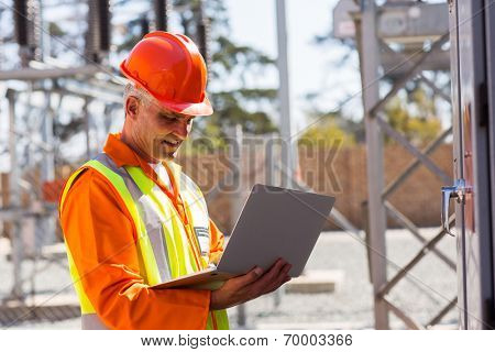 middle aged engineer using laptop in electrical substation