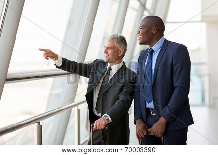 good looking business travelers pointing at airport