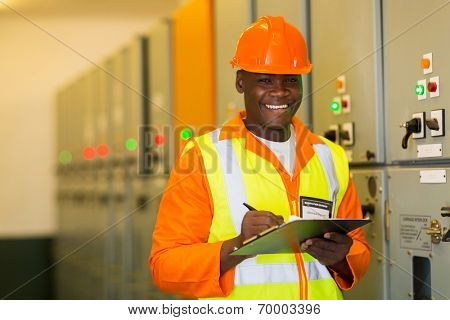happy african american engineer standing in front of control panel