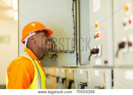 smiling young african american electrician looking at control room