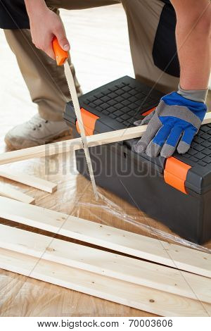 Man Cutting Boards With Handsaw