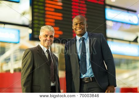 business travelers at airport standing in front of flight information board