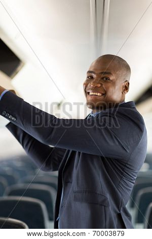 happy african businessman putting luggage into overhead locker on airplane