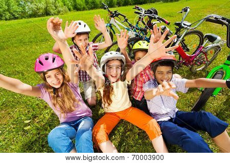 View from top of kids in helmets with hands up
