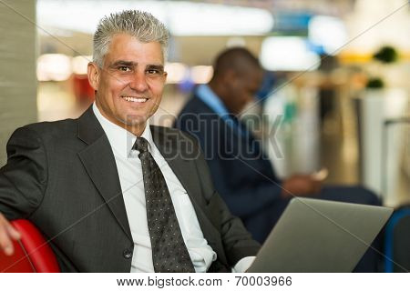 handsome middle aged man waiting at airport lounge