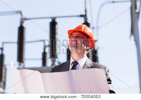 mid age industrial manager working in electric substation