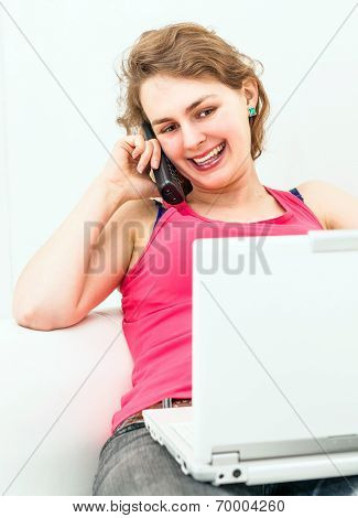 Pretty woman on the couch, using her laptop and talking on the telephone