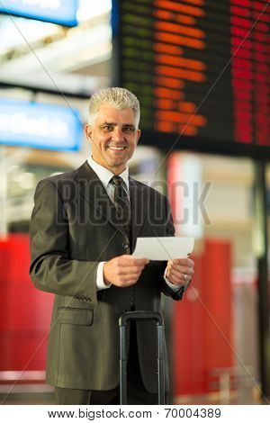 portrait of middle aged businessman in airport holding air ticket