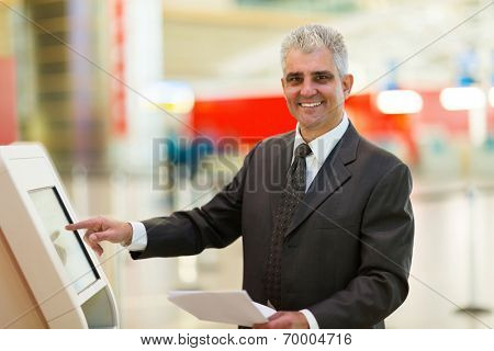 happy mature businessman using self help check in machine at airport