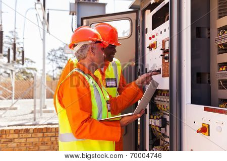 professional electrical engineers adjusting transformer settings
