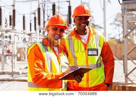 portrait of power company electrical engineers writing on clipboard