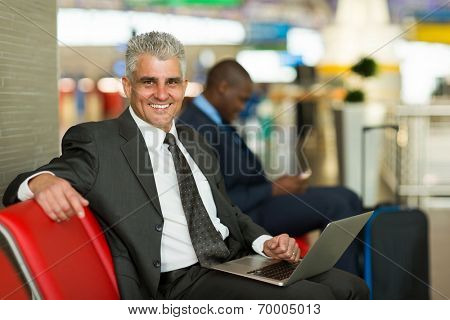 portrait of happy mature business traveler using laptop at airport