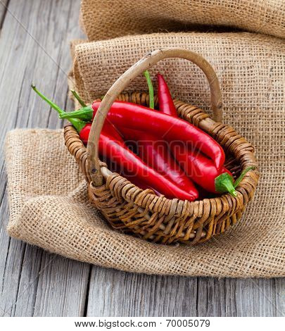 Red Chili Pepper In A Wicker Basket With Burlap On The Wooden Background