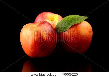 Three Nectarines With Leaf Isolated On Black