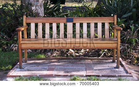 Wooden Park Bench In Shaded Garden Setting