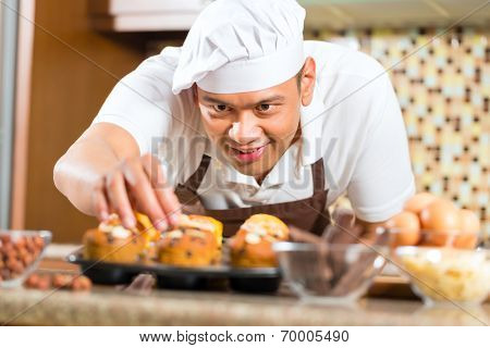 Asian man baking homemade cup cake muffins in his kitchen for dessert