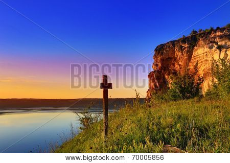 cross near big lake at evening time