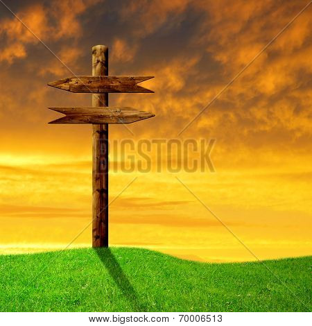 Wooden arrows road sign on meadow in the sunset