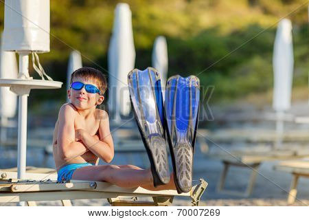 Boy with snorkeling equipment at tropical beach
