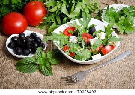 Greek Salad In White Salad Bowl With Cutlery And Vegetables