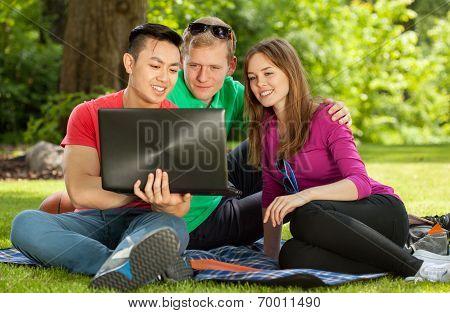 Friends Sitting On Blanket In Park