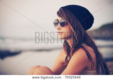Fashion portrait of young hipster woman with hat and sunglasses on the beach at sunset, retro style color tones