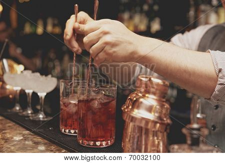 Bartender is stirring cocktails on bar counter, toned image