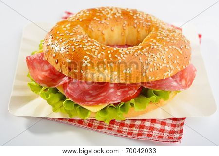 Bagel sandwich with sausage, cheese, and lettuce on a paper plate