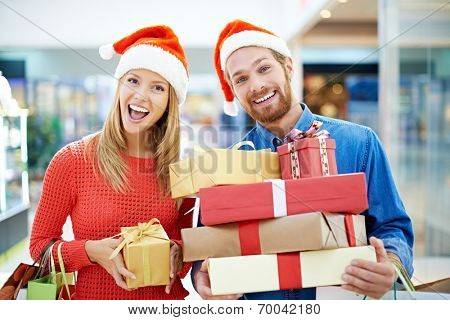 Happy couple posing with Christmas presents