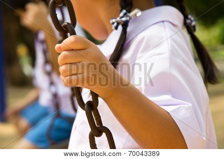 Little child on a swing in the park.