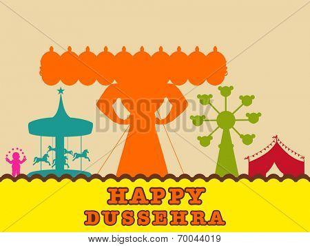 Statue of Ravana in orange in the fair of dusssehra with swings.