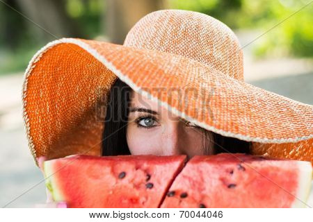 Young stylish lady in a hat with watermelon