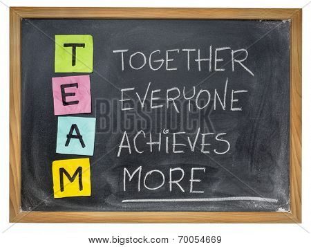 TEAM acronym (together everyone achieves more), teamwork motivation concept, color sticky notes, white chalk handwriting on blackboard