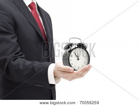 Businessman with an alarm clock in a hand isolated on white.