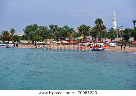 AQABA, JORDAN - MARCH 14, 2014: Boats on the beach of Aqaba in springtime. Glass bottom boats allow tourists to see corals and fishes