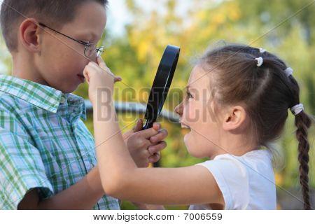 children in early fall park. little boy is looking at joyful little girl through magnifier