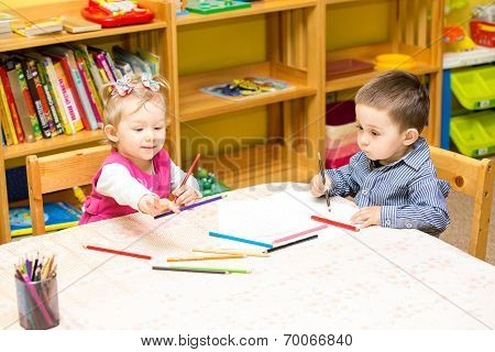 Two Little Kids Drawing With Colorful Pencils In Preschool At The Table. Little Girl And Boy Drawing