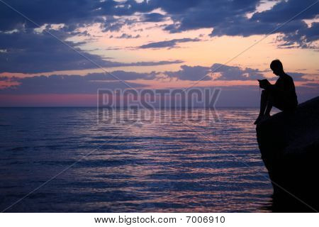 Silhouette Guy Sitting On Breakwater In Evening Near Sea, Reads Book, Wide Angle