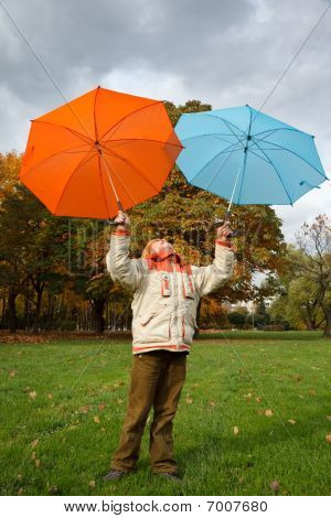 Boy in autumn park. Holds over head two colour umbrellas under cloudy sky.
