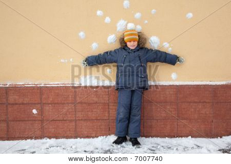 boy kid is standing near wall with snowballs snow stains.
