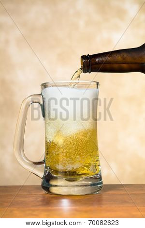 Ice cold, refreshing beer being poured into a classic pint beer mug shows the tasty white froth and golden brew.