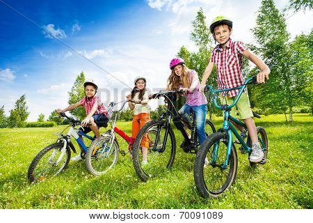 Happy kids in colorful bike helmets holding bikes