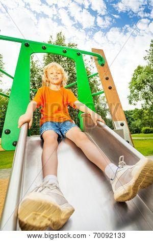 Boy sits on metallic chute and ready to slide