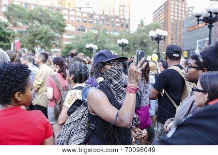 Masked protestor with cell phone cam
