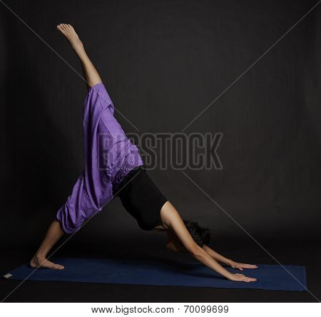 Young Beautiful Yoga Posing On A Black Studio Background.